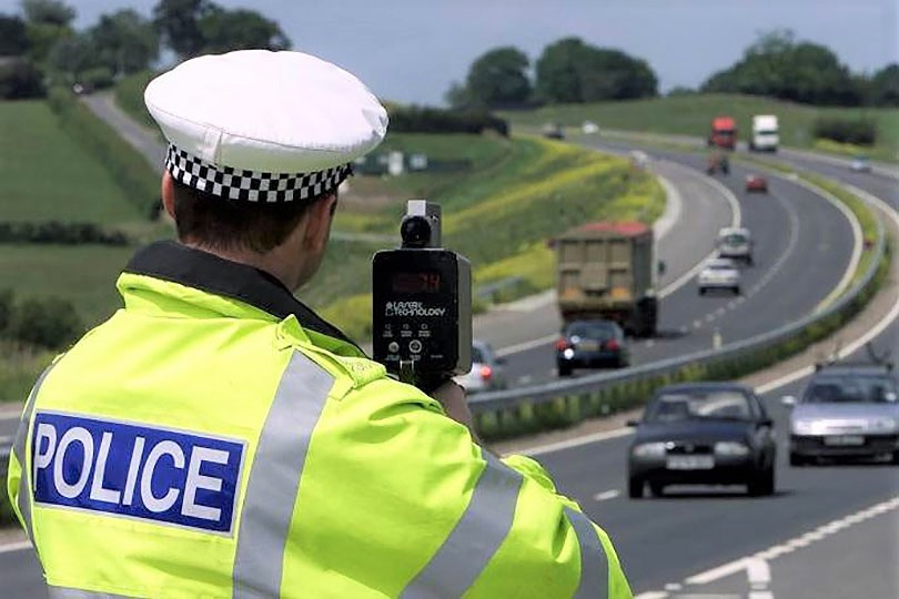 POLICEMAN HUNTING SPEEDING VEHICLES WITH HAND-HELD SPEEDING CAMERA